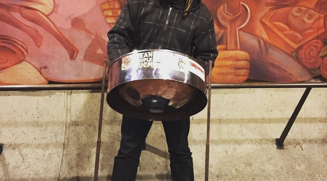 person playing on steel pan drum
