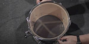 person tuning a drum